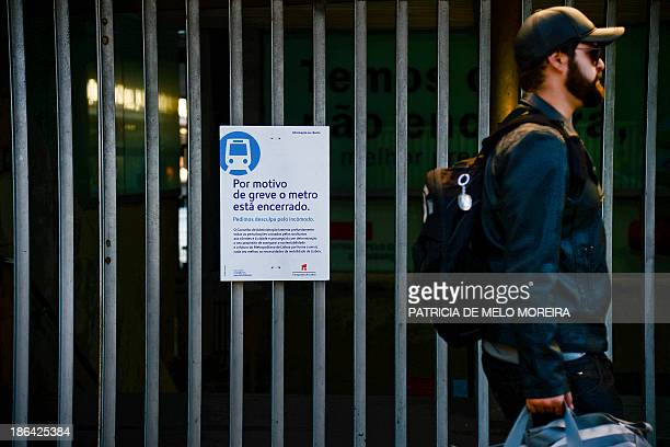 A man walks past a poster reading 'Due to the strike the subway is closed' during the metro strike at Cais do Sodre station in Lisbon on October 31...