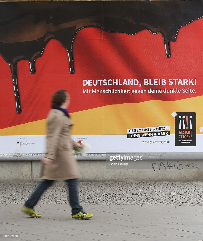 A man walks past a poster showing the German flag with a dripping black portion and that reads: 'Germany, stay strong! With humanity against your dark side,' and below: 'Against hate and baiting, no if and but' on February 9, 2016 in Berlin, Germany. The poster is part of a campaign supported by Germany's Ministry for Families, Seniors, Women and Youth in an effort to encourage more tolerance, particularly of the 1.1 million migrants and refugees that arrived in Germany in 2015. Though a majority of Germans have shown a strong willingness to accept the newcomers and thousands have volunteered to help them, the country has also seen a growing number of attacks, including beatings, arson, vandalism and other violence against refugees and refugee shelters.