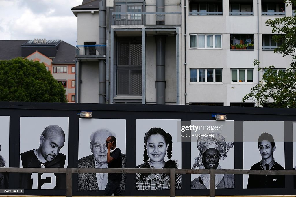 A man walks past a public art exhibition by British photographer Emma Blau in a housing estate in west London on June 27, 2016. 'Face Forward', Blau's large-scale photographic portraits feature local people who will be affected by the huge transformations taking place in their neighbourhood that is undergoing regeneration. / AFP / Odd ANDERSEN / RESTRICTED