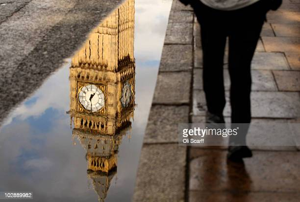 A man walks past a puddle with the reflection of Big Ben's Clock Tower in following A heavy downpour of rain in Westminster on July 14 2010 in London...