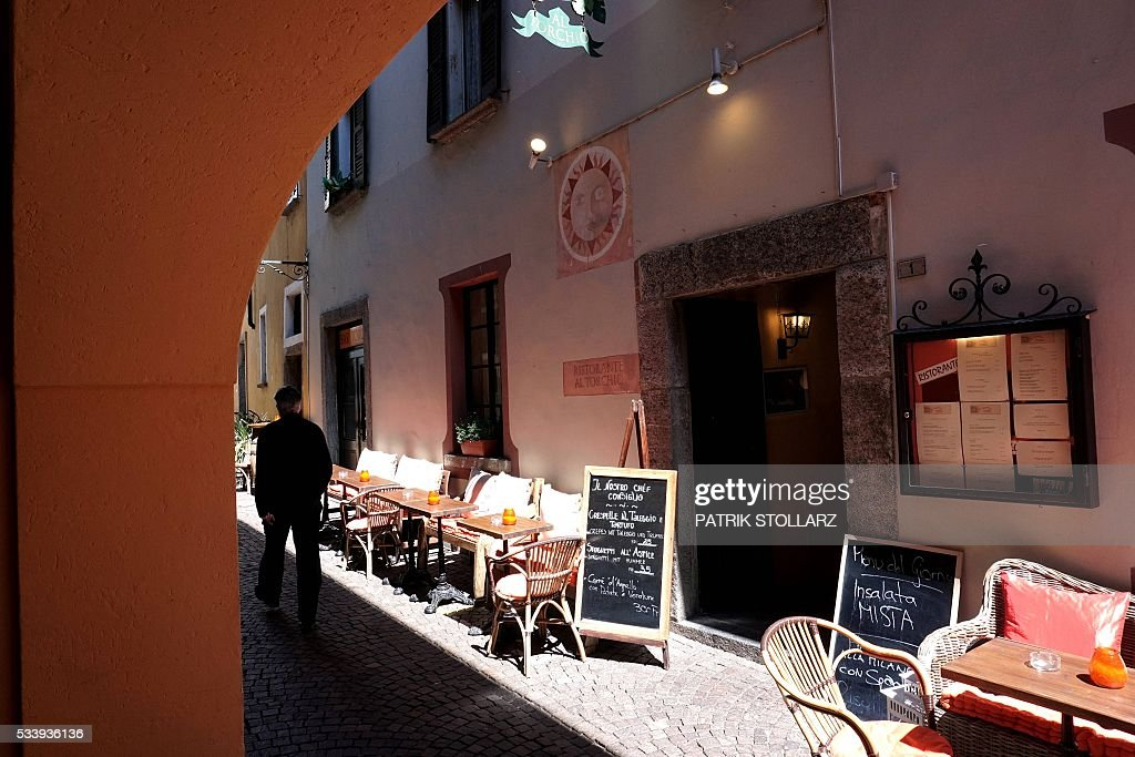 A man walks past a restaurent in Ascona's old town center on May 24, 2016. The German national football team will train here from May 24 until June 3, 2016 for the EURO 2016 taking place in France. / AFP / PATRIK