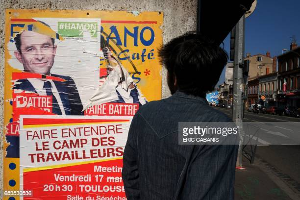 A man walks past a ripped campaign poster of French presidential election candidate for the leftwing Socialist Party Benoit Hamon in Toulouse March...