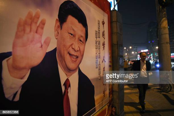 A man walks past a roadside poster of Chinese President Xi Jinping after the closing of the 19th Communist Party Congress in Beijing on October 24...