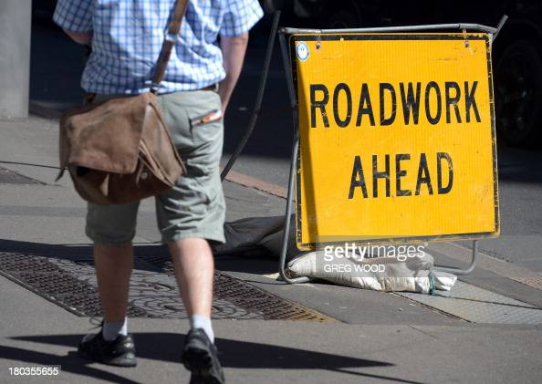 A man walks past a roadwork ahead sign in the central business district in Sydney on September 12 2013 Australia's jobless rate edged up to 58...