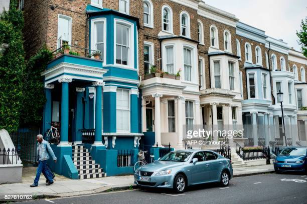 A man walks past a row of houses near Portobello Road Market in the Notting Hill district of west London on August 8 2017 Last week The Bank of...