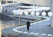 A man walks past a row of lanterns that are part of the light installation Lichtgrenze on the course of the former Berlin wall near the Reichstag...