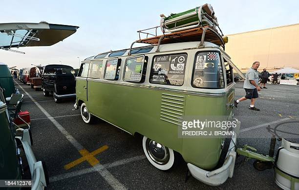 A man walks past a row of Volkswagen's iconic buses displayed at 'Das OCTO Fest 2013' a swap and display gathering for enthusiasts and owners of 1967...