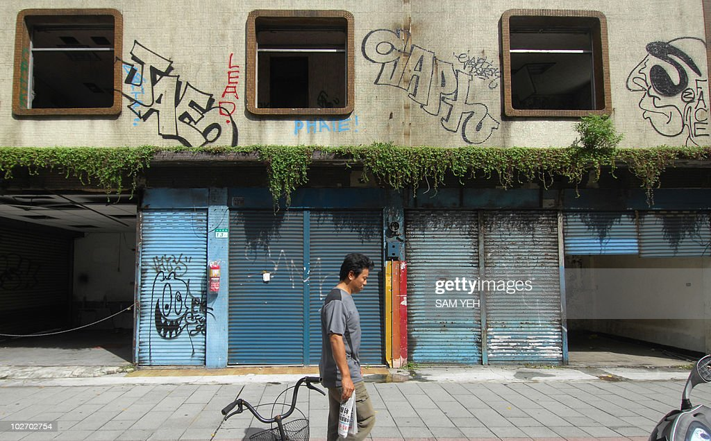A man walks past a rundown building covered with graffiti in Taipei on September 11 2008 Taiwan announced an economic stimulus package worth 56...