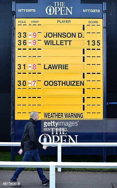 A man walks past a scoreboard showing the leader and the three leading players still to complete their second rounds during a suspension of play on...