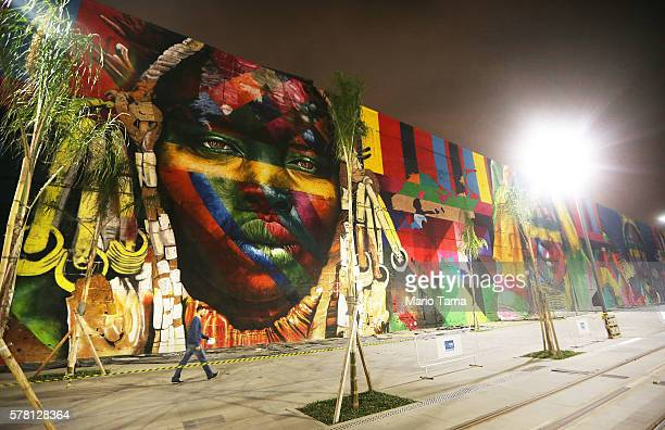 A man walks past a section of a mural depicting indigenous faces being created by Brazilian graffiti artist Eduardo Kobra and assistants in the...