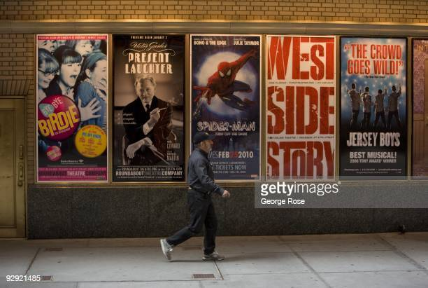 A man walks past a series of Broadway musical billboards outside the Shubert Theatre as seen in this 2009 New York NY early morning cityscape photo