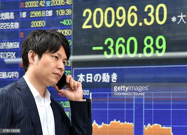 A man walks past a share prices board in Tokyo on June 9 2015 Japan's share prices fell 36089 points to close at 2009630 points at the Tokyo Stock...