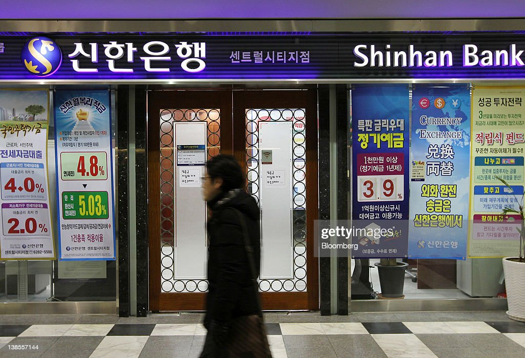 A man walks past a Shinhan Bank branch in Seoul, South Korea, on Thursday, Feb. 9, 2012. Shinhan Financial Group Inc., South Korea's largest financial services group by market value, said profit dropped 13 percent in the fourth quarter as the company set aside more provisions for bad debts. Photographer: SeongJoon Cho/Bloomberg via Getty Images