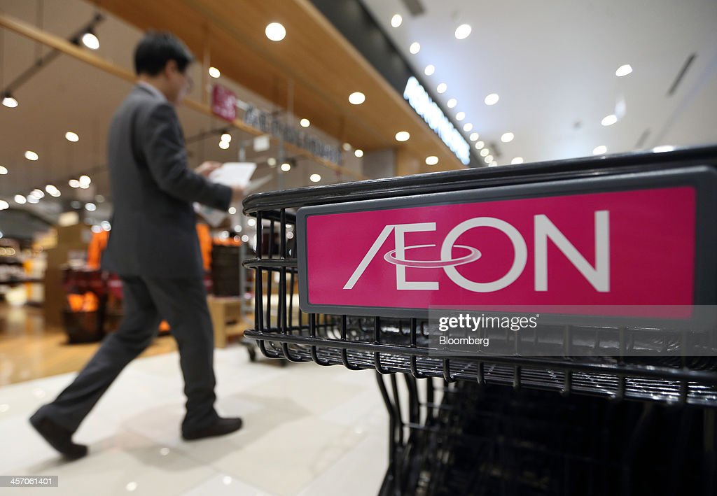 A man walks past a shopping cart bearing the Aeon Co. logo at the Aeon Mall Makuhari Shintoshin shopping mall, operated by Aeon Mall Co., during a media preview ahead of the mall's opening in Chiba, Japan, on Monday, Dec. 16, 2013. Large Japanese businesses pared their projections for capital spending this fiscal year, signaling challenges for Abenomics as a sales-tax increase looms in April. Photographer: Tomohiro Ohsumi/Bloomberg via Getty Images