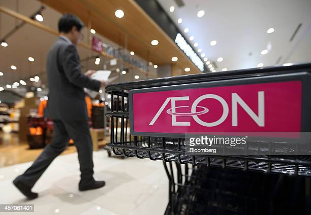 A man walks past a shopping cart bearing the Aeon Co logo at the Aeon Mall Makuhari Shintoshin shopping mall operated by Aeon Mall Co during a media...