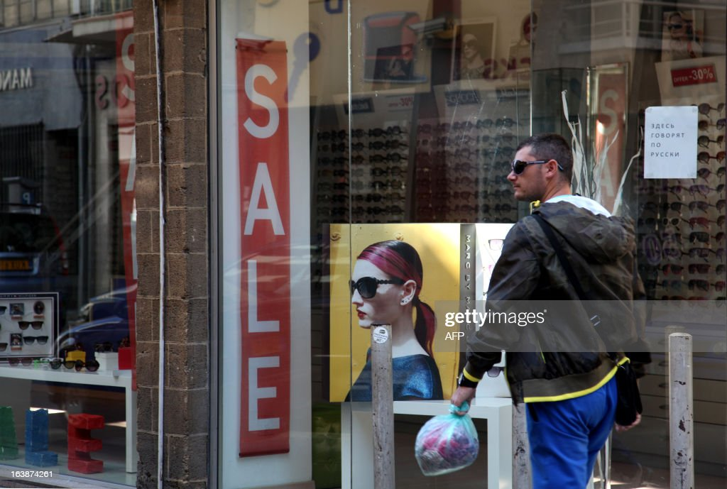 A man walks past a sign advertising sales on the display window of a shop selling eyewear in the Cypriot capital Nicosia on March 17, 2013. The unprecedented decision to tap all bank accounts in Cyprus as part of an EU bailout is a threat to the entire economy of the Mediterranean island, an important financial centre, analysts say.