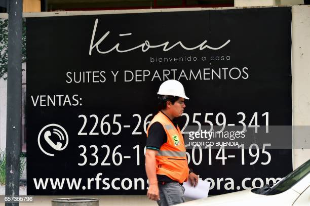 A man walks past a sign offering apartments for sale in Quito on March 24 2017 The collapse of the real estate market in Ecuador is not the cause of...