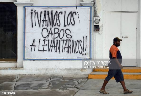 A man walks past a sign reading 'Go Los Cabos to raise' after hurricane Odile in San Jose Los Cabos Baja California State Mexico on September 20 2014...