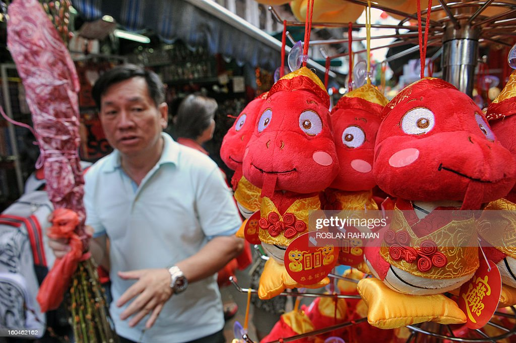 A man walks past a stall selling snake themed stuffed toys ahead of the upcoming Chinese lunar New Year of the snake in Chinatown of Singapore on February 1, 2013. Chinese celebrate the Chinese lunar New Year of the snake on February 10.