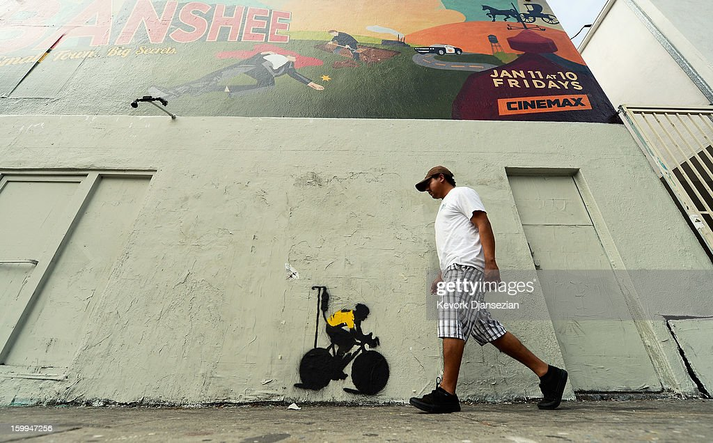 A man walks past a stencil graffiti depicting cyclist Lance Armstrong in a yellow jersey, the traditional garb of the seven-time Tour De France winner, attached to an IV drip on January 23, 2013 in Los Angeles, California. Armstrong recently admitted to using performance enhancing drugs after being found guilty by the United States Anti-Doping Agency and stripped of his titles.