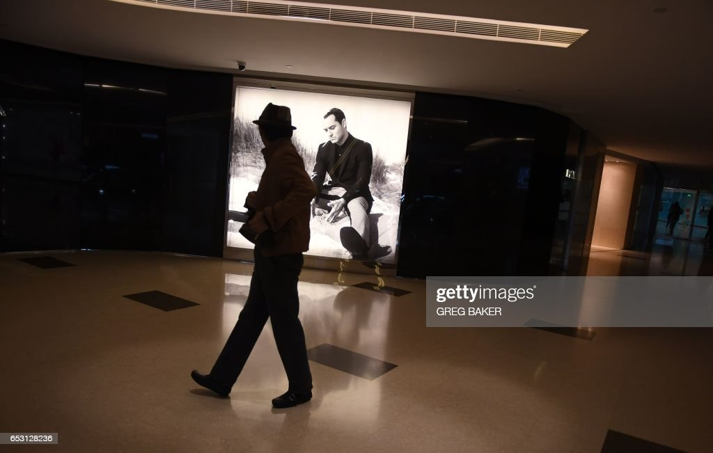 A man walks past a store at a shopping mall in Beijing on March 14, 2017. China retail sales growth decelerated to 9.5 percent year-on-year in January and February, government data showed on March 14, as policymakers work to keep the world's second-largest economy on a stable growth path. /
