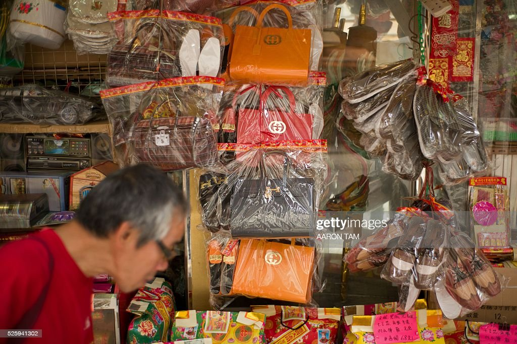A man walks past a store selling paper replicas of items used as offerings for deceased relatives and displaying paper luxury bags in Hong Kong on April 29, 2016. Luxury fashion brand Gucci has warned Hong Kong shops selling paper handbags as 'offerings' for the dead not to market items resembling their products. / AFP / AARON TAM