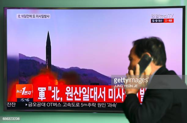 TOPSHOT A man walks past a television screen showing file footage of a North Korean missile launch at a railway station in Seoul on March 22 2017 A...