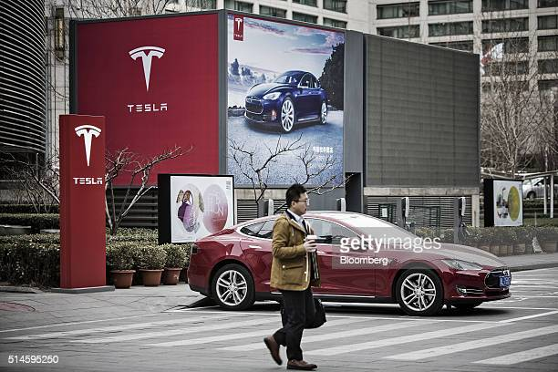A man walks past a Tesla Motors Inc Model S electric automobile at one of the company's electric charging stations near a shopping mall in Beijing...