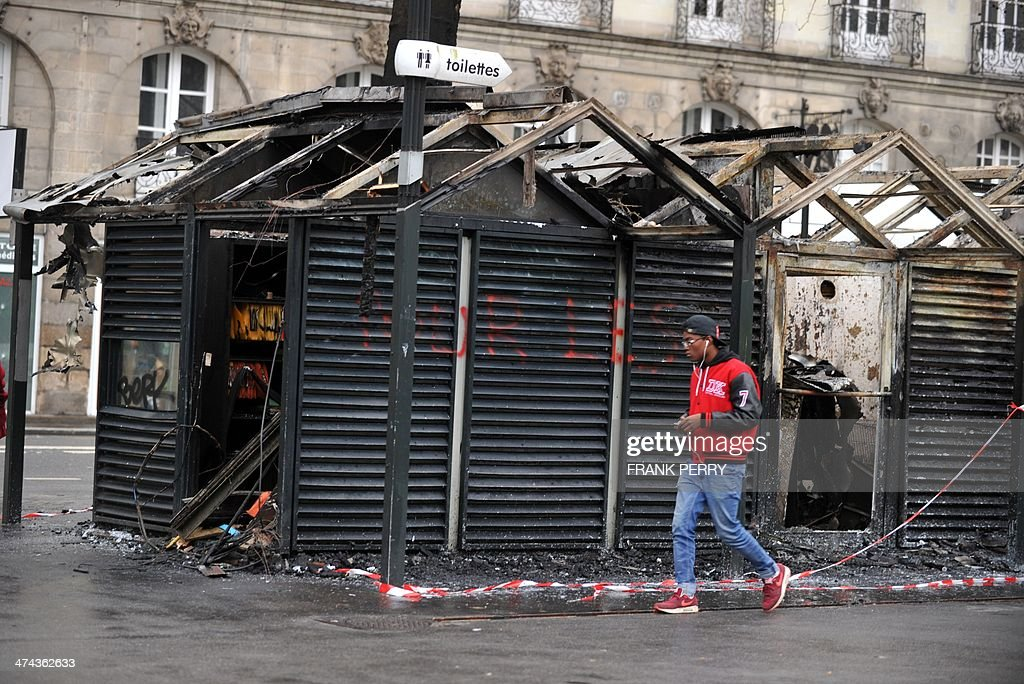 A man walks past a tramway station in Nantes, western France, on February 23, 2014 which was burnt down by protesters opposed to plans to build the Notre-Dames-des-Landes airport for the French city of Nantes. Protesters smashed shop windows on February 22 and hurled paving stones at police, who answered with tear gas and rubber bullets. Tens of thousands of protesters against building the airport on protected swampland swarmed the western city's Petite Hollande square, the latest in a string of demonstrations against the pet project of Prime Minister Jean-Marc Ayrault.