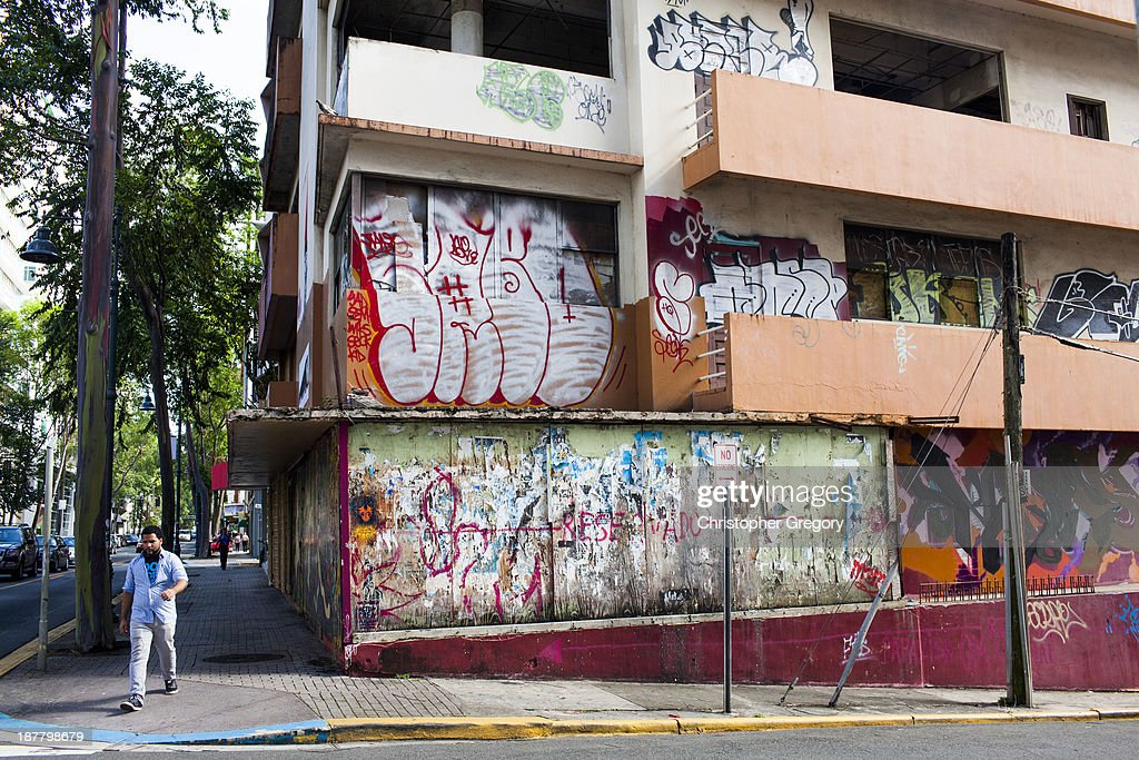 A man walks past a vacant building on November 12 2013 in the Santurce neighborhood of San Juan Puerto Rico The island territory of the United States...