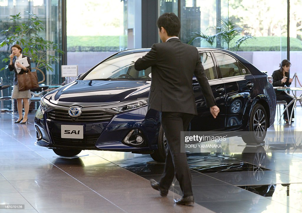 A man walks past a vehicle at the showroom of the head office of Japan's auto giant Toyota Motor in Tokyo on November 6, 2013. Toyota said on November 6 that its half-year net profit soared 82.5 percent while it raised its annual earnings forecast as a weak yen and improving sales in North America boosted its bottom line. AFP PHOTO/Toru YAMANAKA