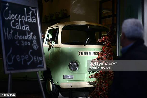 A man walks past a Volkswagen kombi or bulli camping van used to decorate an Italian icecream shop 'Gelateria' on January 6 2014 in Rome AFP PHOTO /...