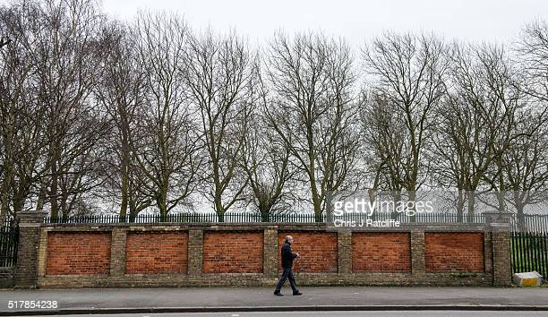 A man walks past a wall and over the top of the Grade II listed Victorian Crystal Palace Subway that is hidden under the A212 road at Crystal Palace...