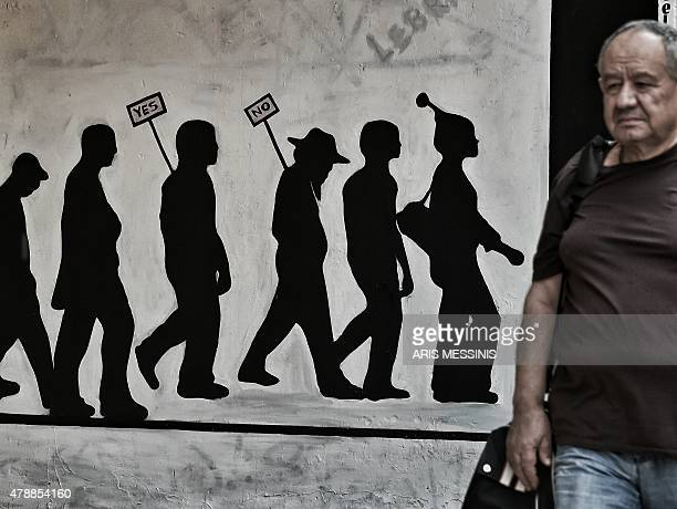 A man walks past a wall bearing graffitti concerning Greece's referendum on the latest offer of a debt deal by the country's EUIMF creditors in...