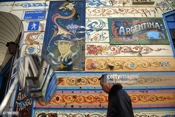 A man walks past a wall decorated with flowers and plants at Carlos Gardel's street in the Abasto neighborhood in Buenos Aires Argentina on June 19...
