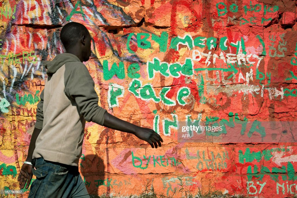 A man walks past a wall sprayed with graffiti reading 'We need peace in Kenya' in Nairobi's Kibera slum on February 27, 2013. Kenya is gearing up for presidential, gubernatorial, senatorial elections on March 4, the first since bloody post-poll violence five years ago in which more than 1,100 people died after contested results.