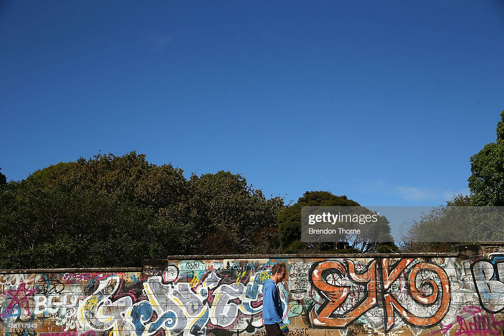 A man walks past a wall strewn with graffiti on May 8, 2014 in Sydney, Australia. The Grafitti Control Amendment Act passed in the NSW legislative council yesterday includes tougher penalties a the ability for local courts to enforce community clean up duty on offenders.