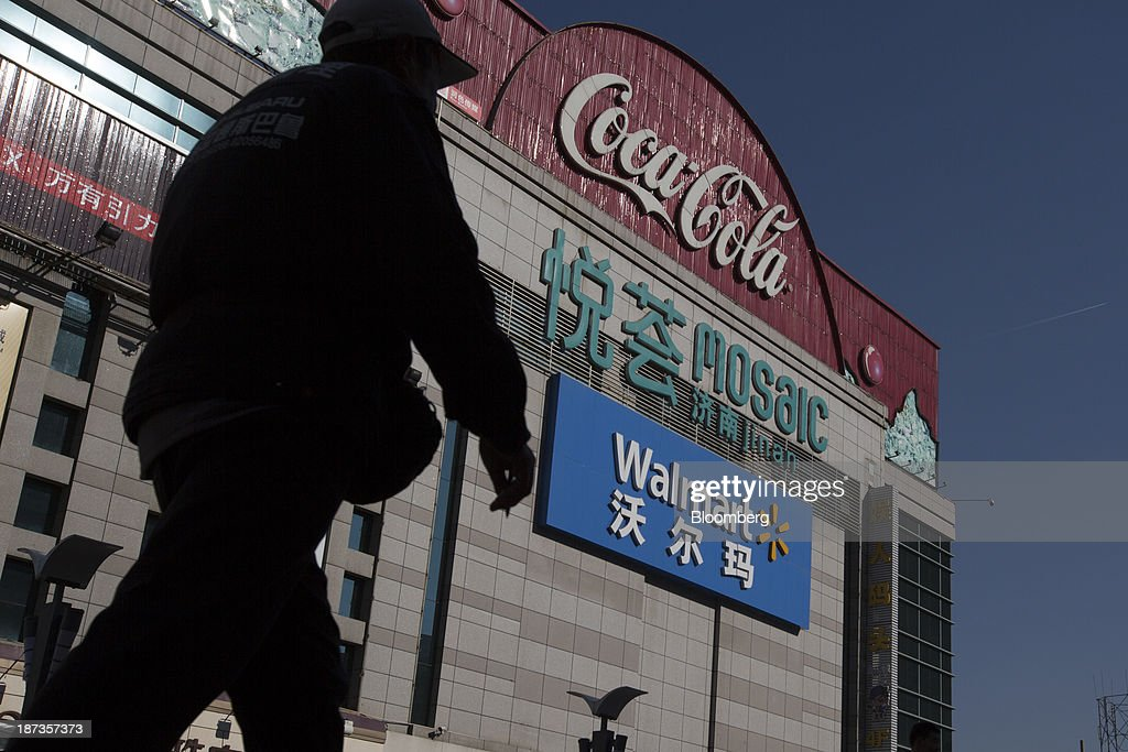 A man walks past a Wal-Mart Stores Inc. outlet in Jinan, China, on Thursday, Nov. 7, 2013. The third plenary session of the 18th Communist Party of China Central Committee will be held from Nov. 9 to Nov. 12 in Beijing. Photographer: Brent Lewin/Bloomberg via Getty Images