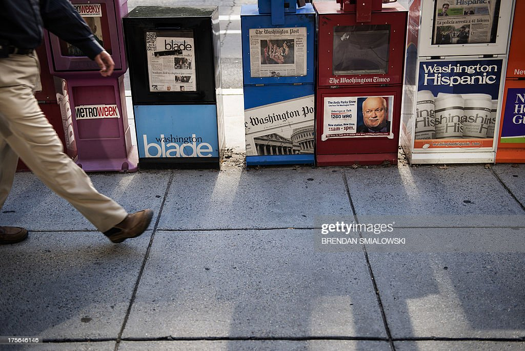 A man walks past a Washington Post newspaper box (C) beside the empty box of competitor Washington Times (2nd-L) outside the Washington Post August 5, 2013 in Washington, DC, after it was announced that Amazon.com founder and CEO Jeff Bezos had agreed to purchase the Post for USD 250 million. Multi-billionaire Bezos, who created Amazon, which has soared in a few years to a dominant position in online retailing, said he was buying the Post in his personal capacity and hoped to shepherd it through the evolution away from traditional newsprint. AFP PHOTO/Brendan SMIALOWSKI