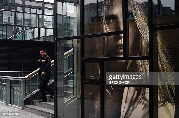 A man walks past a window display at a fashion outlet in Beijing on October 22 2014 The global economic recovery is beset by 'downside risks' China's...