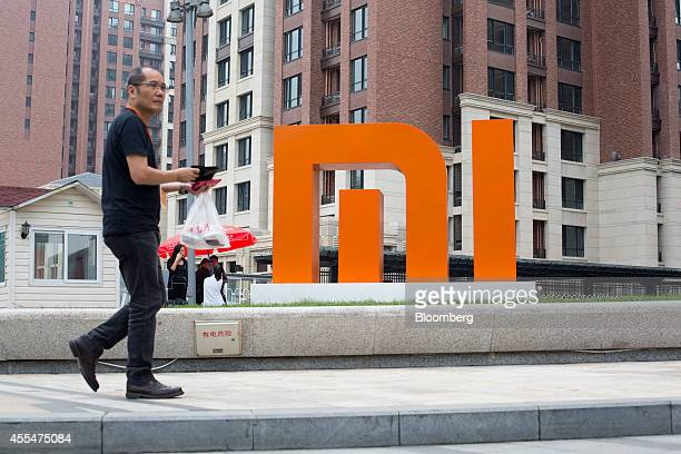 A man walks past a Xiaomi Corp logo displayed outside the company's headquarters in Beijing China on Friday Sept 12 2014 Xiaomi Chief Executive...