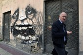 A man walks past abandoned businesses in central Athens on April 2 2015 AFP PHOTO / LOUISA GOULIAMAKI