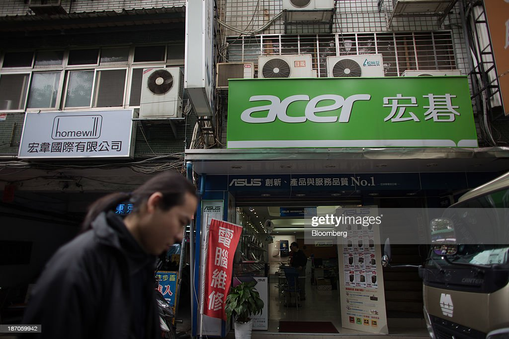 A man walks past Acer Inc. signage displayed outside an electronics store on Bade Road in Taipei, Taiwan, on Wednesday, Nov. 6, 2013. Acer, Taiwans second-largest computer maker, plunged to a 12-year low in Taipei trading after announcing a record loss, job cuts and the resignation of J.T. Wang as chief executive officer. Photographer: Lam Yik Fei/Bloomberg via Getty Images