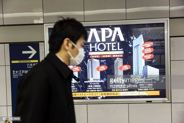 A man walks past advertising for the APA hotel group at a subway station in Tokyo on February 1 2017 Japanese organisers of this month's Asian Winter...