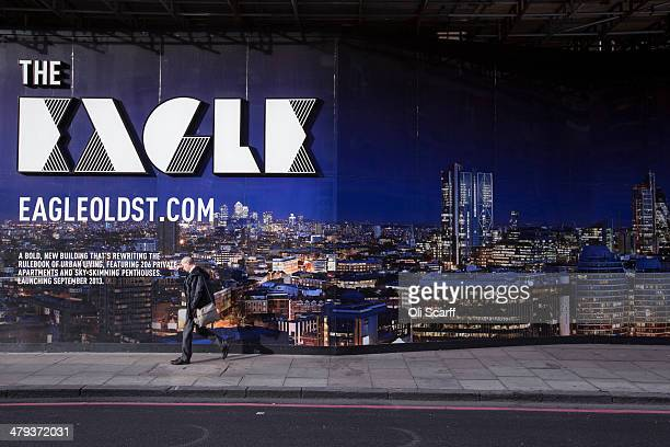 A man walks past an advertisement for a new city centre highrise residential development on March 18 2014 in London England The Government's 'Help to...