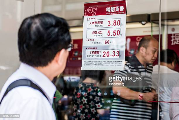 A man walks past an advertisement for renminbi and New Zealand dollar deposits at a Bank of China Ltd branch in Hong Kong China on Wednesday Aug 12...