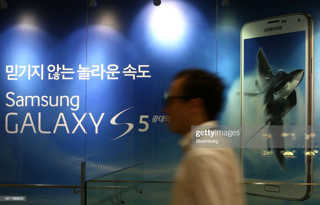 A man walks past an advertisement for the Samsung Electronics Co. Galaxy S5 smartphone at the company's d'light store in Seoul, South Korea, on Monday, July 7, 2014. Samsung Electronics is scheduled to report operating profit and sales figures on July 8. Photographer: SeongJoon Cho/Bloomberg via Getty Images