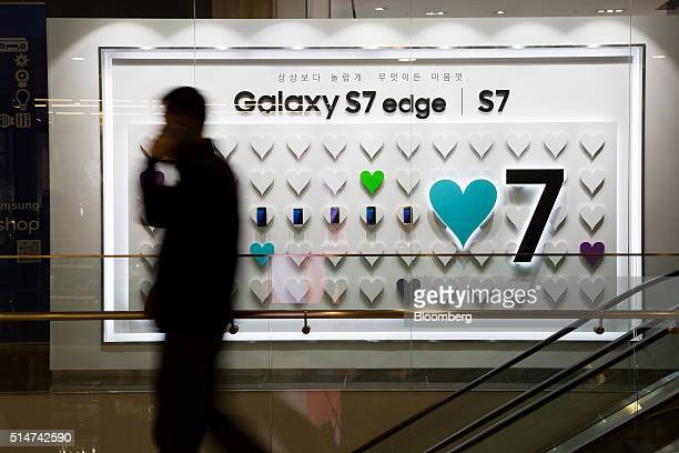 A man walks past an advertisement for the Samsung Electronics Co Galaxy S7 and S7 Edge smartphone outside the company's Dlight flagship store in...