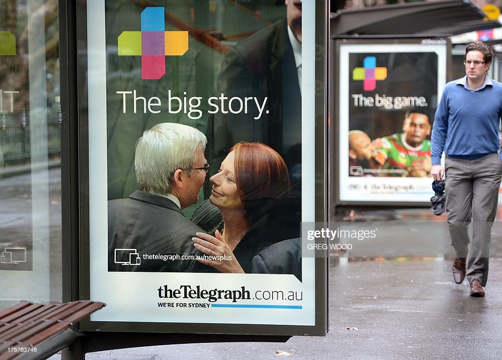 A man walks past an advertising board for media tycoon Rupert Murdoch's key tabloid the Sydney Daily Telegraph at a bus shelter in Sydney on August 8...