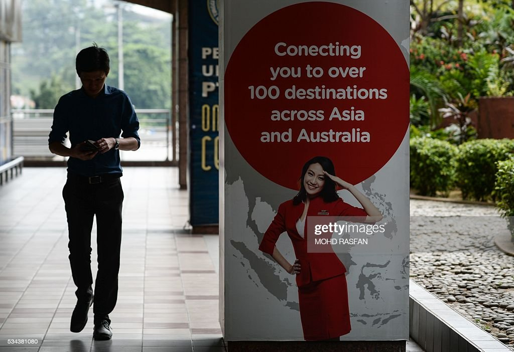 A man walks past an AirAsia advertisement at Kuala Lumpur Sentral railway station in Kuala Lumpur on May 26, 2016. Malaysia's Budget carrier AirAsia was expected to announce its first quarter results on the back of lower oil prices on May 26. / AFP / MOHD